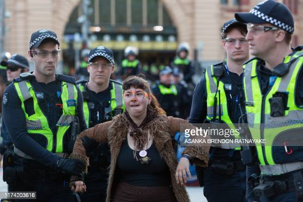A demonstrator is arrested by police during a Extinction Rebellion protest in Melbourne on October 7 2019 Extinction Rebellion activists began...