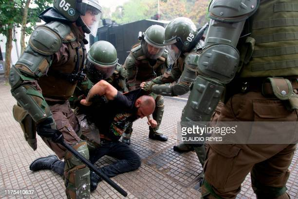 A demonstrator is arrested by riot policemen during a protest in downtown Santiago on October 12 within the commemoration of the Day of the Race