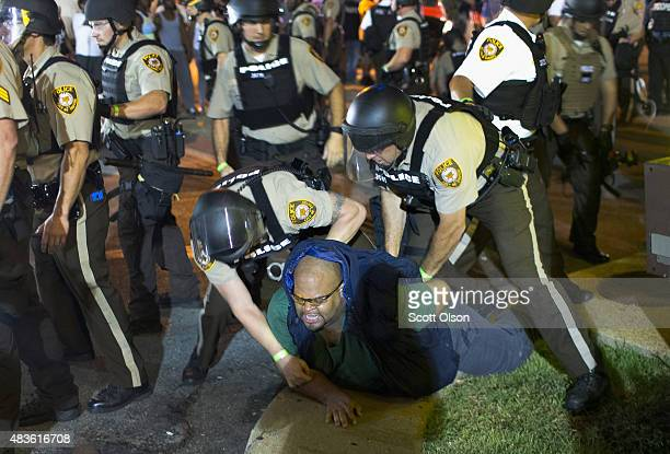 A demonstrator is arrested during a protest marking the oneyear anniversary of the shooting of Michael Brown along West Florrisant Street on August...