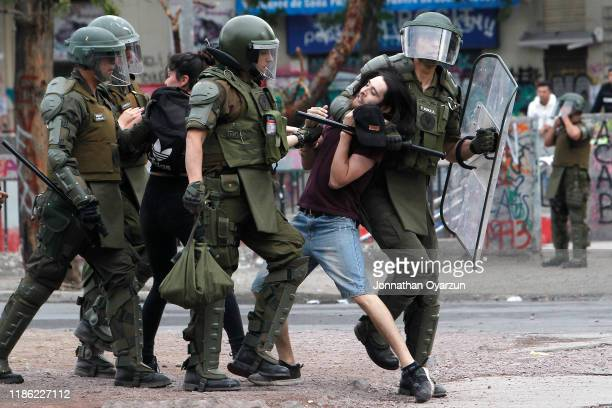 A demonstrator is arrested during protests against president Piñera at Plaza Italia on December 2 2019 in Santiago Chile To reduce social unrest and...