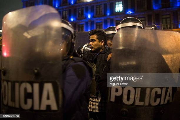 A demonstrator is captured by policemen outside Mexico's National Palace after a confrontation with riot police after Mexico's government announced...