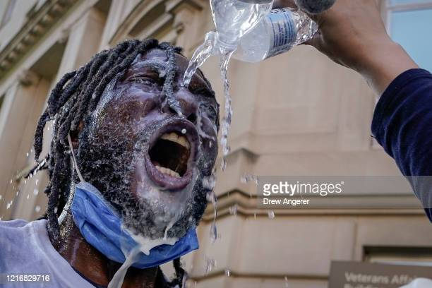 A demonstrator is doused with water and milk after being hit with pepper spray from law enforcement during a protest on June 1 2020 in downtown...
