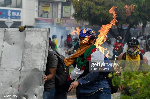 Demonstrator is hit by a Molotov cocktail thrown during clashes with riot police officers during a protest against a proposed government tax reform...