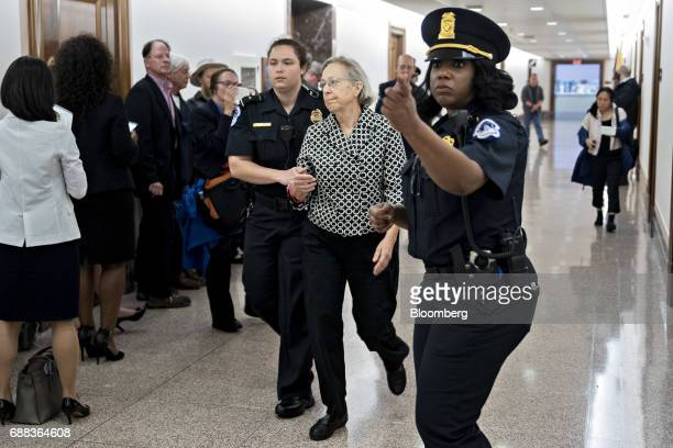 A demonstrator is led away by US Capitol police after interrupting a Senate Energy and Natural Resources nomination hearing in Washington DC US on...
