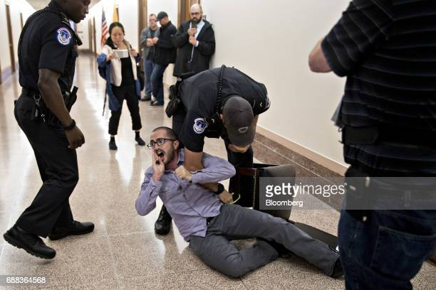 A demonstrator is locked to a chair while being detained by US Capitol police after interrupting a Senate Energy and Natural Resources nomination...