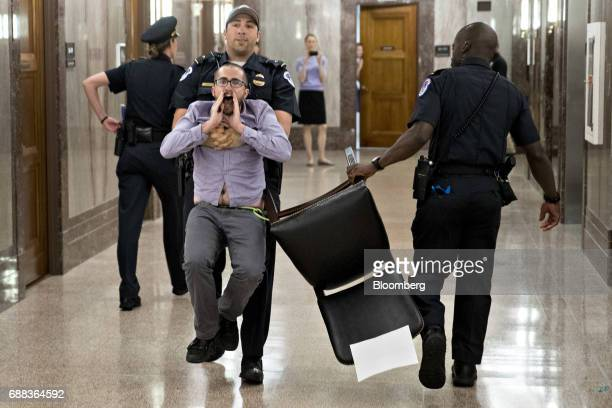 A demonstrator is locked to a chair while being led away by US Capitol police after interrupting a Senate Energy and Natural Resources nomination...