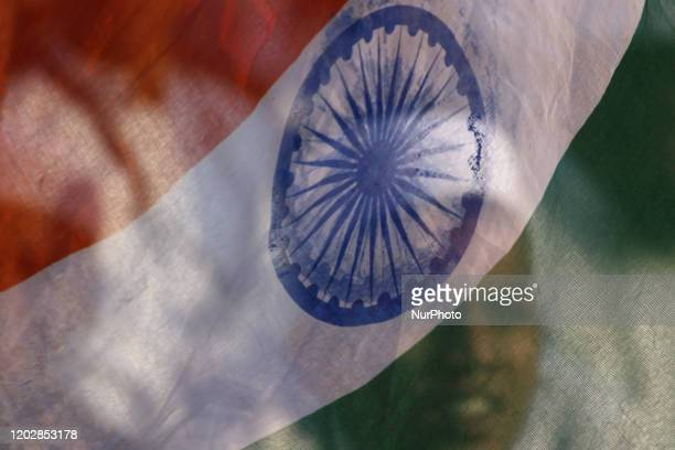A demonstrator is seen through an Indian national flag during a protest against the Citizenship Amendment Act and National Register of Citizens and...