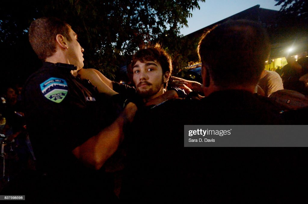 A demonstrator is shoved by police during a rally for the removal of a Confederate statue, coined Silent Sam, on the campus of the University of Chapel Hill on August 22, 2017 in Chapel Hill North Carolina.