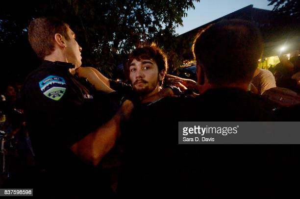 A demonstrator is shoved by police during a rally for the removal of a Confederate statue coined Silent Sam on the campus of the University of Chapel...