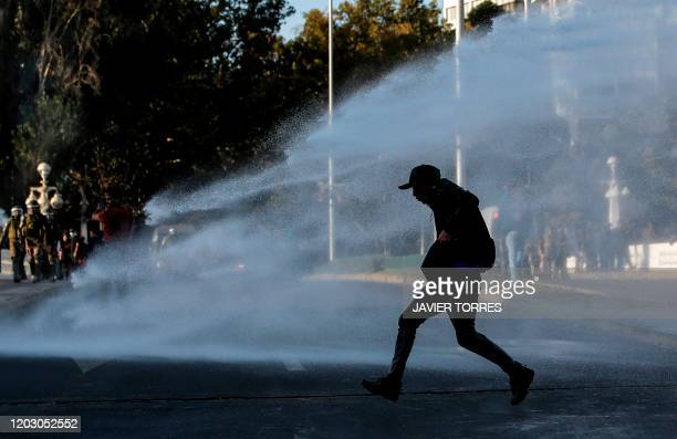 Demonstrator is sprayed with a water cannon on February 24, 2020 during clashes with riot police which erupted in a protest against Chile's President...