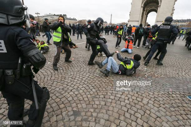A demonstrator is stopped by the French riot police near the Arc de Triomphe during an antigovernment demonstration called by the Yellow Vests...