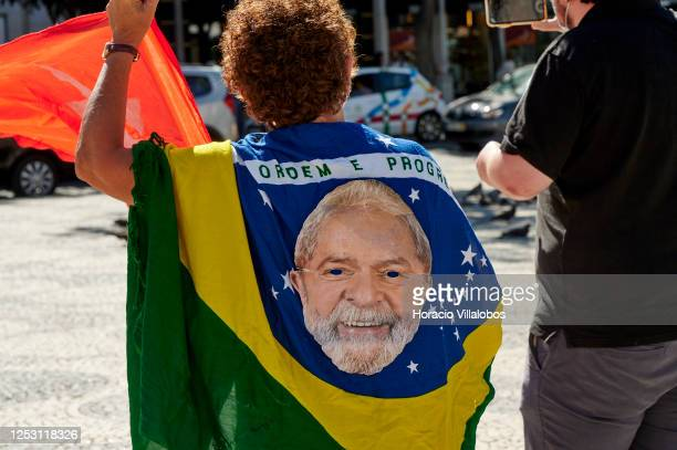 Demonstrator is wrapped in a Brazilian flag that bears the face of former President Lula as Brazilian residents gather in Praça Rossio to demand the...