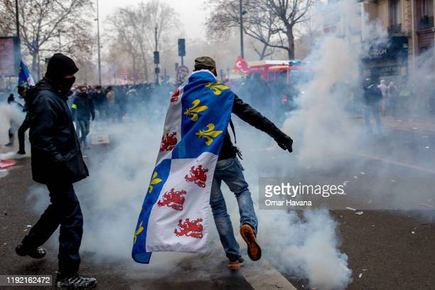 A demonstrator kicks a canister of tear gas thrown by the police during the first day of an indefinite general strike on December 05 2019 in Paris...
