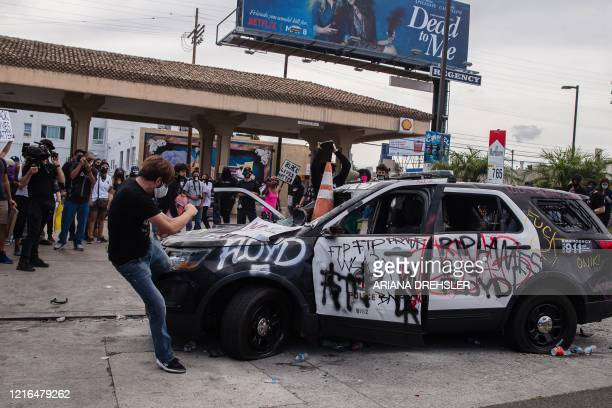 TOPSHOT A demonstrator kicks a damaged police vehicle in Los Angeles on May 30 2020 following a protest against the death of George Floyd an unarmed...