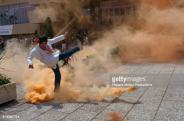 A demonstrator kicks away a smoke bomb during a protest staged by medical students in front of the Palais des Festivals in Cannes France