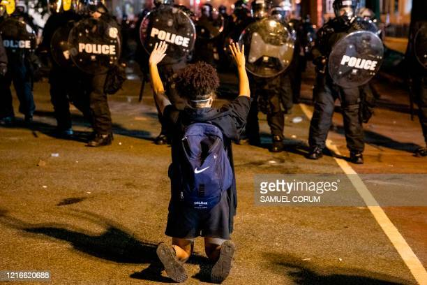 TOPSHOT A demonstrator kneels and raises her hands facing a police line in front of the White House while protesting the death of George Floyd at the...