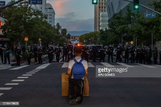 TOPSHOT A demonstrator kneels in front of a Police line in Downtown Los Angeles on May 30 2020 during a protest against the death of George Floyd an...