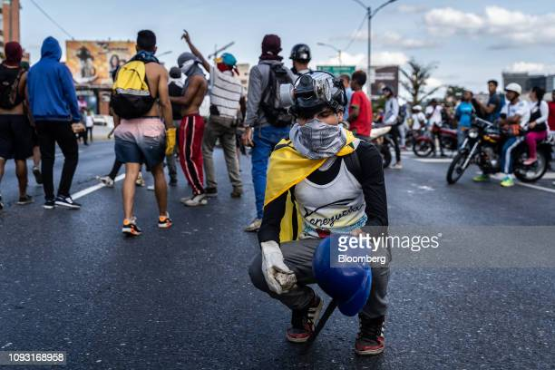 A demonstrator kneels while holding a rock on the Francisco Fajardo Highway during a proopposition protest in Caracas Venezuela on Saturday Feb 2...