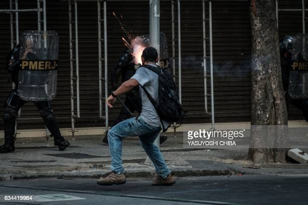 TOPSHOT A demonstrator launches a firework at Military Police during clashes following a protest against the privatization of Rio de Janeiro state...