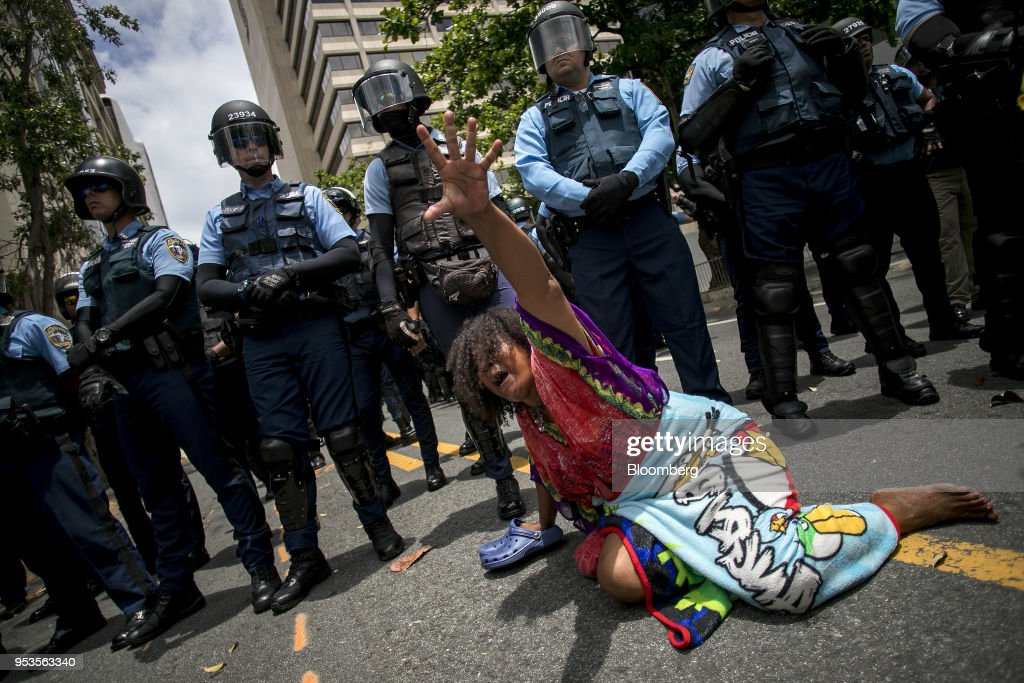 A demonstrator lays in front of riot police officers during a protest against austerity measures in the Hato Rey neighborhood of San Juan, Puerto Rico, on Tuesday, May 1, 2018. Puerto Rico demonstrators battled police on San Juan's streets as they marched against proposed cuts to retirement benefits and looser labor laws as the bankrupt island seeks to reduce $74 billion of debt. Photographer: Xavier Garcia/Bloomberg via Getty Images