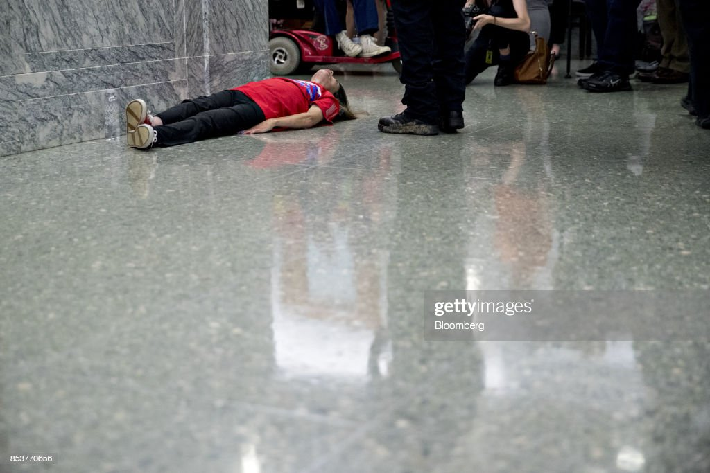 A demonstrator lays on the ground outside Senate Finance Committee hearing to consider the Graham-Cassidy-Heller-Johnson proposal in Washington, D.C., U.S., on Monday, Sept. 25, 2017. Senators sponsoring a last-ditch Obamacare repeal bill raced to save it from near-certain death Sunday, circulating a new version aimed at winning over several GOP holdouts. Photographer: Andrew Harrer/Bloomberg via Getty Images