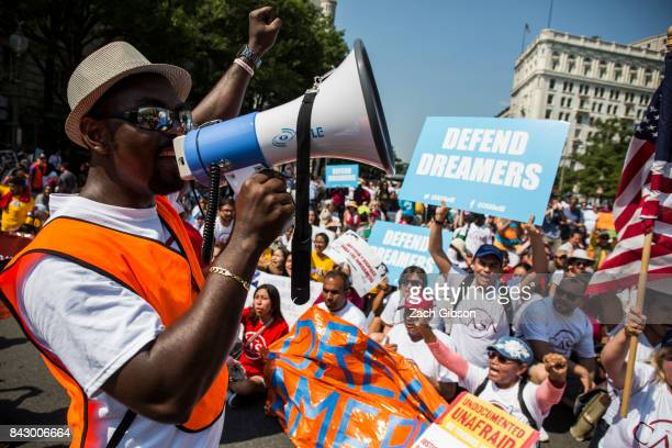 A demonstrator leads a chant during a demonstration in response to the Trump Administration's announcement that it would end the Deferred Action for...