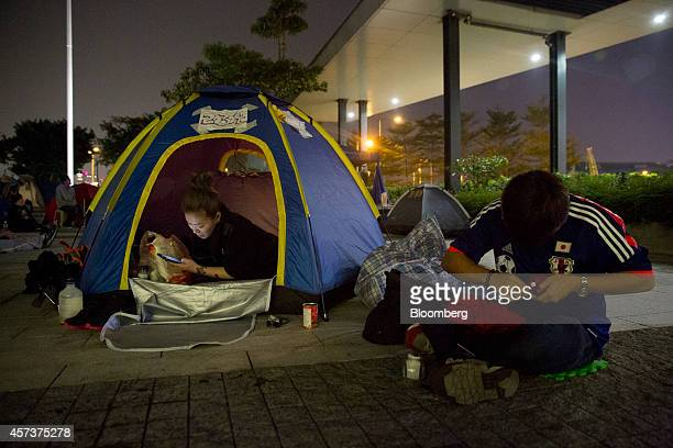 A demonstrator left holds a mobile phone inside a tent outside Chief Executive Leung Chunying's office in the Admiralty business district Hong Kong...