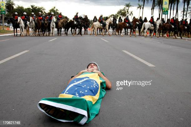 Demonstrator lies on the street wrapped with a Brazilian flag during a rally near Brasilia's Estadio Nacional Mane Garrincha to protest against the...