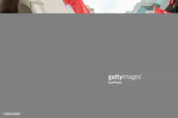 Demonstrator lifts a copy of the Tunisian constitution as others shout slogans, during a demonstration held in the capital Tunis, Tunisia, on...