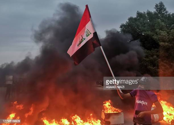 Demonstrator lifts a national flag by burning tyres amid clashes between Iraqi anti-government protesters and supporters of firebrand Shiite cleric...