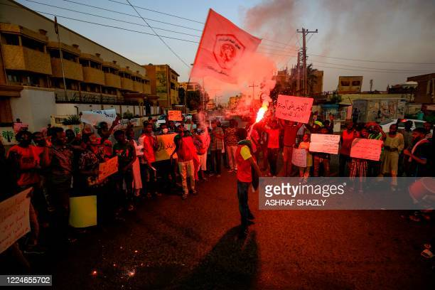 A demonstrator lights a flare while chanting slogans during a protest outside the Sudanese Professionals Association in the Garden City district of...