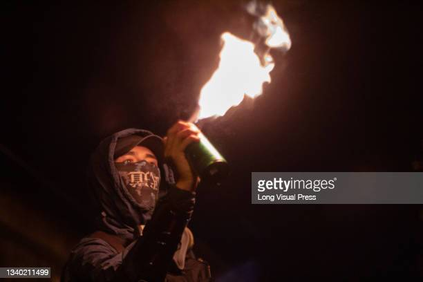 Demonstrator lights up a can of spray paint in fire as the Villa Luz CAI police station were police officers tortured Javier Ordonez on September 9...