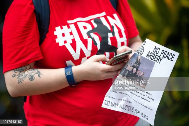 A demonstrator looks at a phone outside the Glynn County Courthouse where Gregory and Travis McMichael attended a preliminary hearing on June 4 2020...
