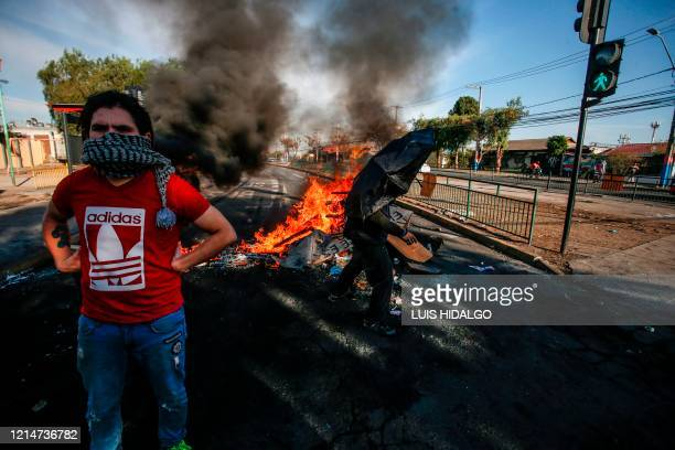 Demonstrator looks on during clashes with riot police within a protest against Chilean President Sebastian Pinera's government amid the COVID-19...