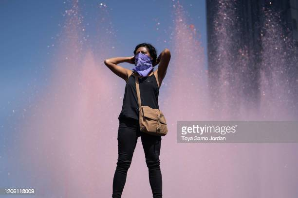 A demonstrator looks on next to a fountain dyed with red ink during a rally on International Women's Day on March 8 2020 in Mexico City Mexico