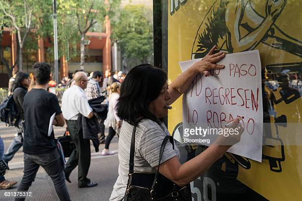 A demonstrator makes a sign during a protest against the gasoline price hike in Mexico City Mexico on Monday Jan 9 2017 The government is letting gas...