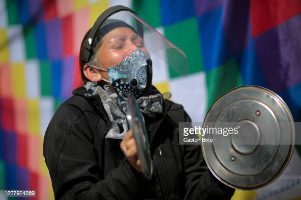 A demonstrator makes noise with pots' lids during a protest in front of the Supreme Electoral Tribunal during a hunger strike against the...