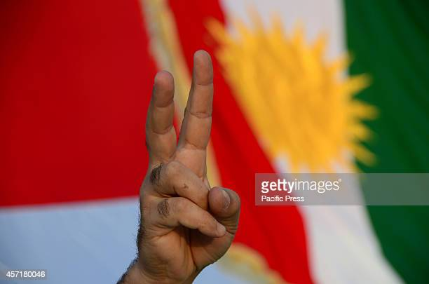 A demonstrator makes the 'victory' sign standing in front of a Kurdish flag Kurdish people that live in Athens organised a demonstration in support...