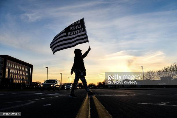 Demonstrator marches, holding a Black Lives Matter flag, during the sixth night of protests over the shooting death of Daunte Wright by a police...