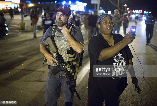 A demonstrator marking the oneyear anniversary of the shooting of Michael Brown confronts a member of the Oath Keepers during a protest along West...