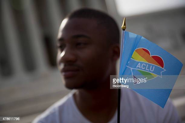 Demonstrator Michael Abney holds a miniature rainbow American Civil Liberties Union flag outside the US Supreme Court in Washington DC US on Friday...