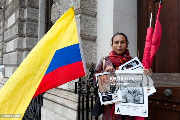 Demonstrator next to a Colombia flag holding placards with photos of social leaders killed in Colombia during the protest Demonstrators gathered...