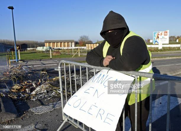 A demonstrator of the Yellow Vests movement stands by a sign reading Angry French on a barrier on November 18 2018 on a roundabout in DouchylesMines...