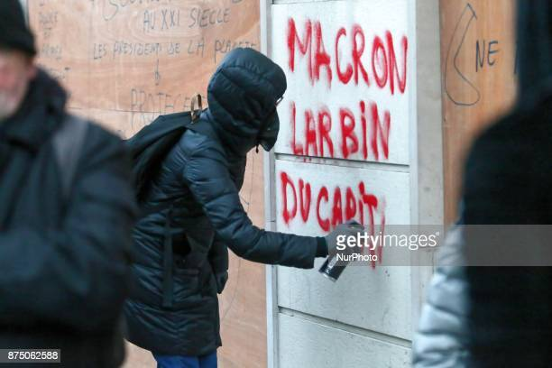 Demonstrator of ultraleft writes on a wall 'Macron lackey of capital' during a demonstration as part of a nationwide protest day against the...