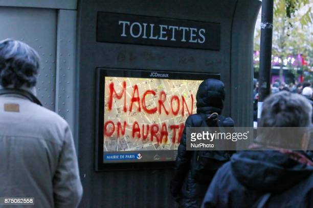 Demonstrator of ultraleft writes on a wall 'Macron well get you' during a demonstration as part of a nationwide protest day against the government's...