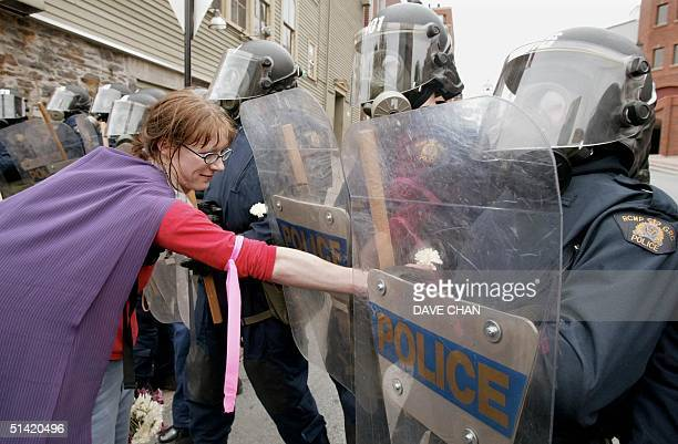 A demonstrator offer a policeman a flower 15 June 2002 on the final day of G7 Finance Ministers meeting in Halifax Canada Police fired tear gas...