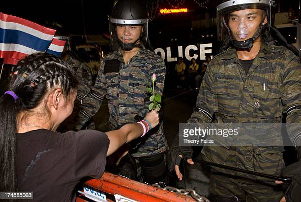 A demonstrator offers a rose to a antiriot policeman Thousands of demonstrators have defied warnings of a crackdown from the Thai Prime minister...