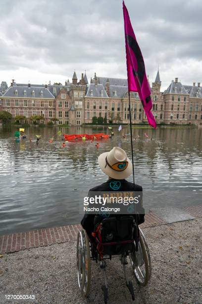 A demonstrator on a wheelchair watches as people get into Lake Hofvijver next to the parliament in protest during the demonstration in The Hague on...