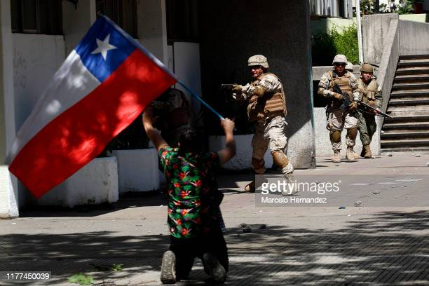 A demonstrator on his knees waves a Chilean flag as military officers clash with demonstrators during a protest on October 21 2019 in Santiago Chile...