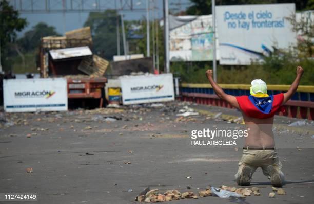 A demonstrator on the Francisco de Paula Santander International Bridge in Cucuta Colombia gestures at Venezuelan security forces blocking the bridge...